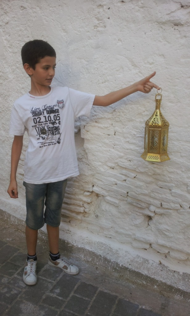Mohsinne's son holds up a lantern recently made by his father.