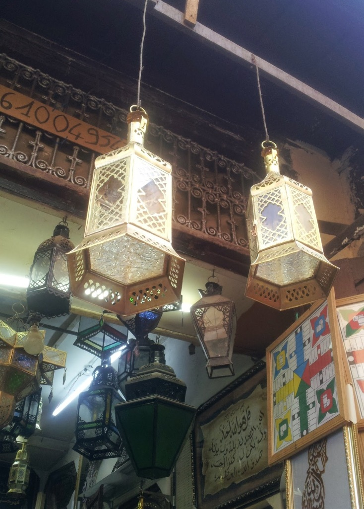 Two recently made lanterns hang above Mohssine's shop. A board game Mohssine made hangs on the wall.